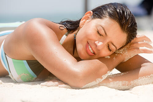 BEautiful woman lying at the beach over sand